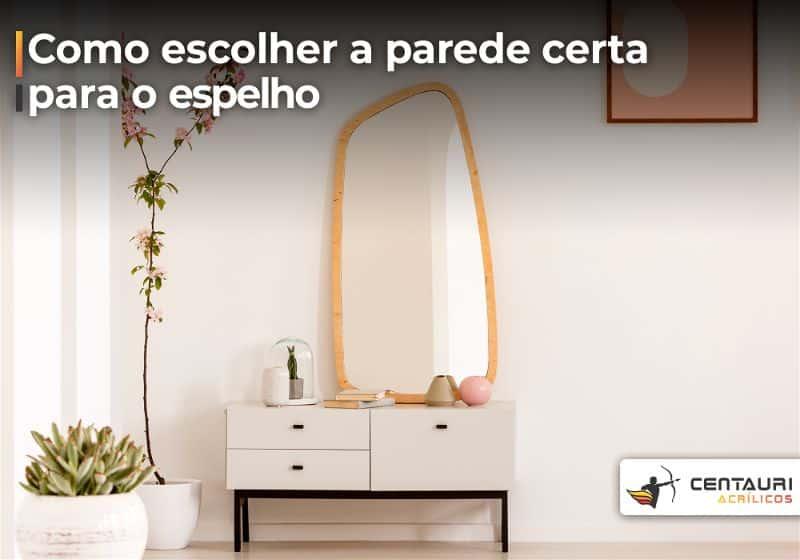 Ambiente com pequena cômoda e um espelho sobre