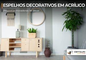 Ambiente com móvel, planta decorativas e espelho redondo com moldura pendura em parede
