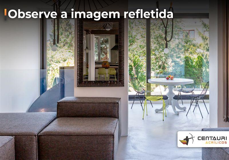 Ambiente de casa que lembra uma sala de estar com espelho quadrado com moldura pendurado em parede
