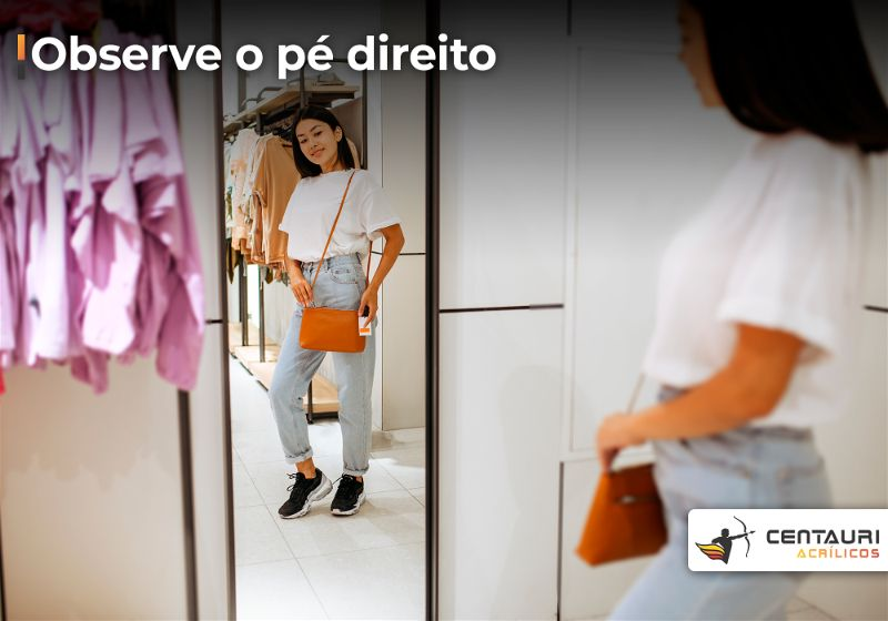 Mulher com um bolsa se olhando em espelho grande e retangular apoiado no chão
