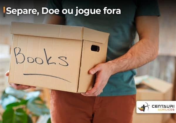 Homem carregando uma caixa de livros velhos para doação