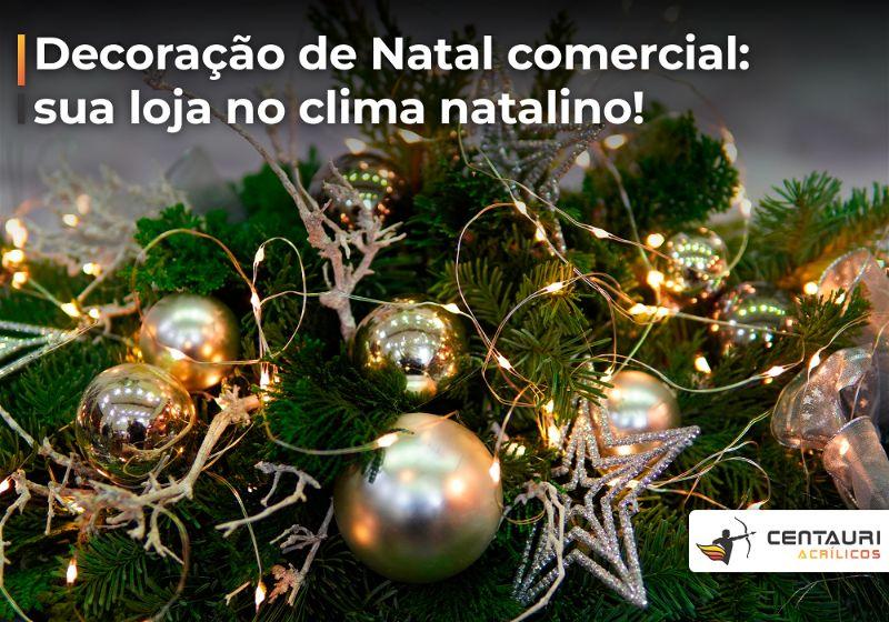 Enfeites de natal como bolinhas e estrelas douradas sobre galhos de pinheiro, junto com pisca-pisca aceso