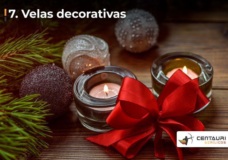 Duas mini velas em potinhos de vidro ao lado de laço vermelho e bolinhas de natal