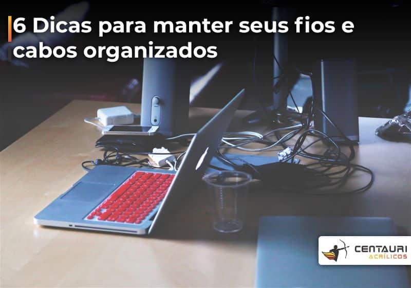 Mesa com notebook e equipamentos eletrônicos, bem como, cabos desorganizados