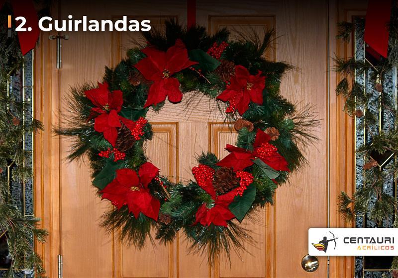 Guirlanda decorada com laços vermelhos, pendurada em porta de madeira