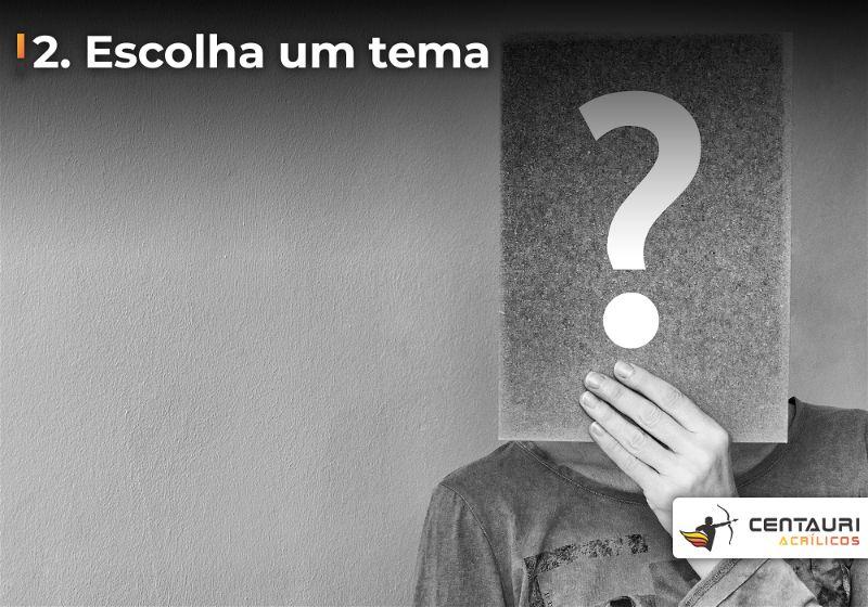 Imagem em preto e branco com uma pessoa segurando placa em frente o rosto e com um ponto de interrogação