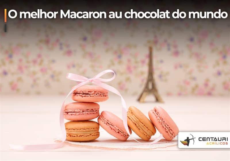 Macarons de rosa e laranja pastel em primeiro plano e em segundo plano uma torre Eiffel de decoração